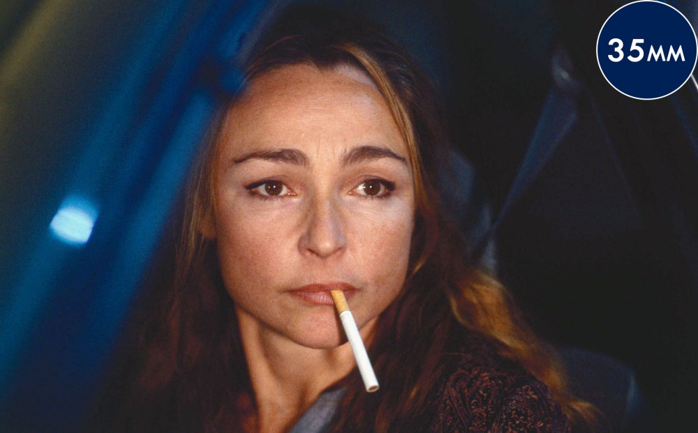 Actress Catherine Frot gazes off with a cigarette in her mouth.