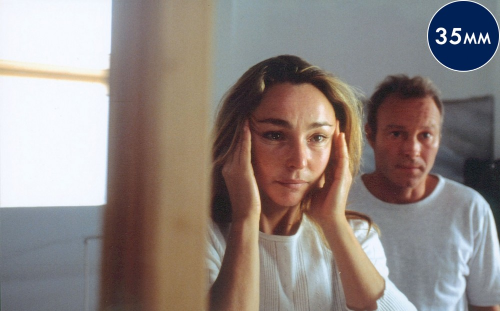 With tears in her eyes, actress Catherine Frot puts her hands to her temples.