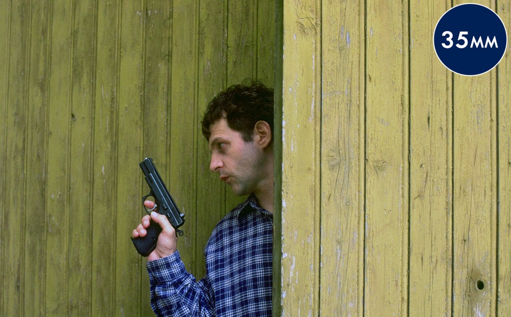 Director and actor Lucas Belvaux hides behind a wall, holding a gun.