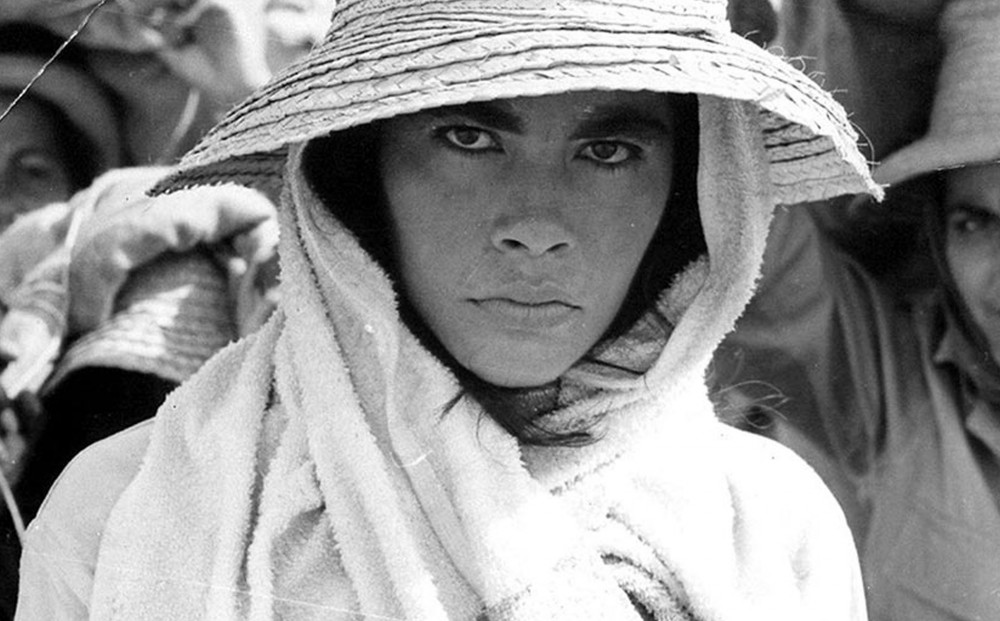 A woman wearing white and a straw hat.