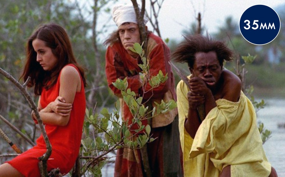 Three people stand in a marsh: a woman in a red dress, sitting on a branch with her arms crossed over her shoulders, and two men clutching and leaning on tree branches.