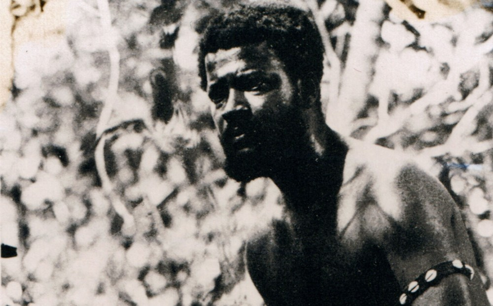 The face and shoulders of a shirtless man, wearing an armband decorated with cowry shells.