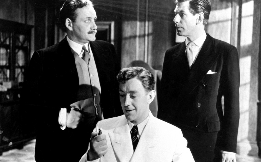 Actor Alec Guinness wears a white suit, and sits; two men in black suits stand on either side of him.