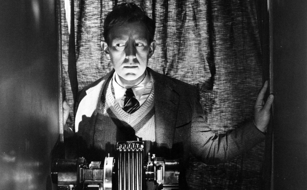 Actor Alec Guinness stands by lab equipment, his face lit from below with intense shadows.