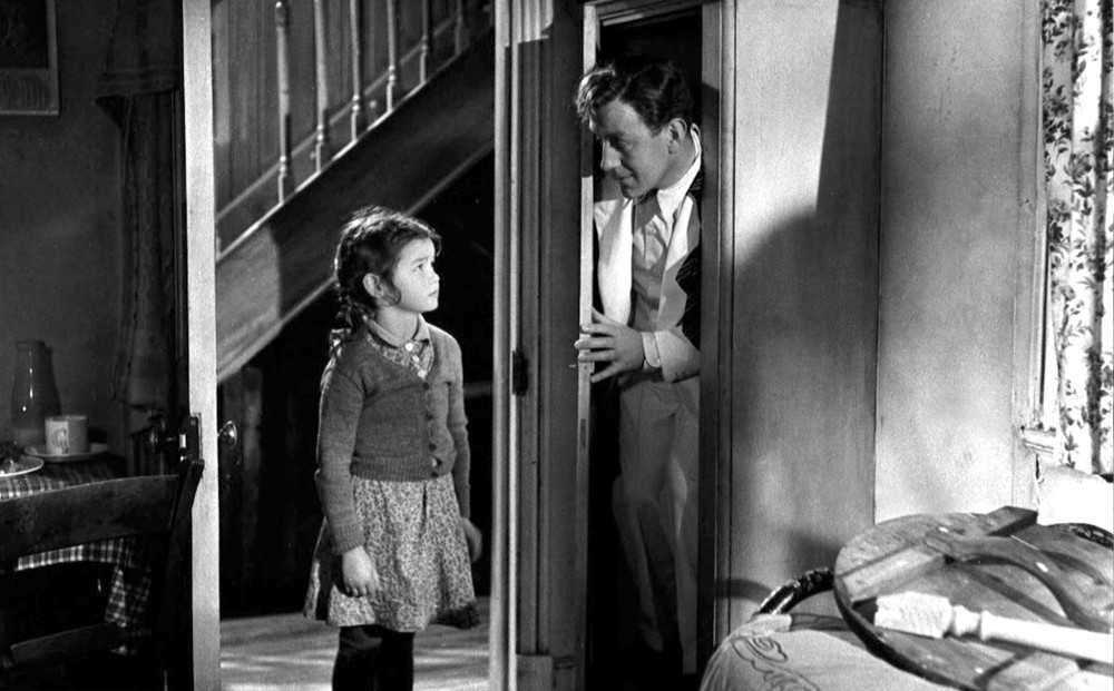 A little girl looks at Alec Guinness, who pokes his head out of the bedroom closet where he appears to be hiding.