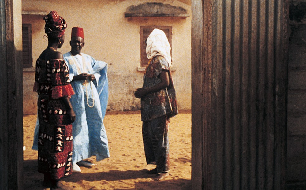 A man and two women converse, all wearing traditional Senegalese clothing.