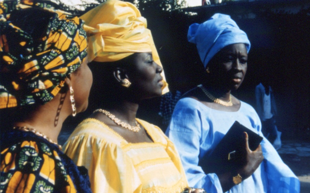 Three women talk and walk, all wearing traditional Senegalese clothing.