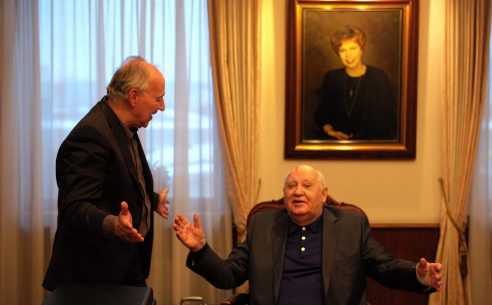 Mikhail Gorbachev, seated, and Werner Herzog, standing, gesture towards each other with their arms spread.