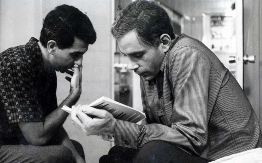 Two men sit facing each other, one reading a book.