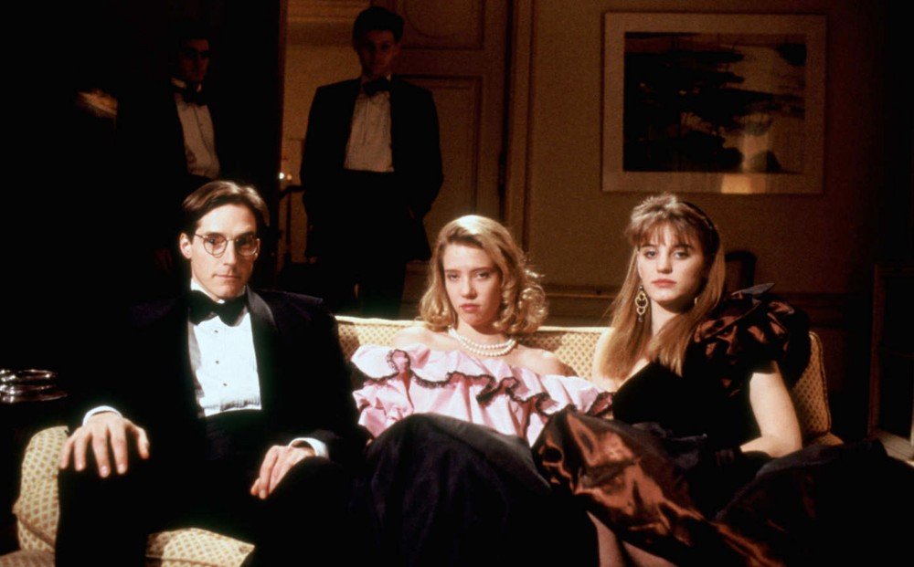 A man and two women in fancy party clothes sit on a couch.