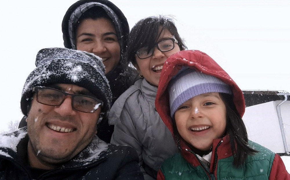 A family wearing winter clothing, dusted with snow, smiles at the camera for a selfie.