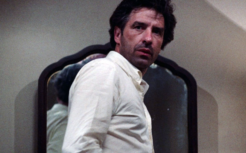 Actor John Cassavetes, wearing a white button-down shirt; a mirror is behind him.