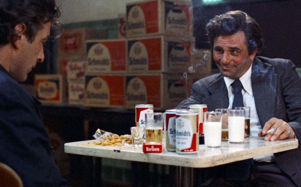 Actors  John Cassavetes and Peter Falk sit at a table that is covered in cans and cups of beer, and cups of milk; the latter smokes a cigarette.