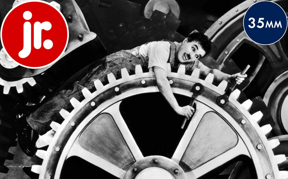 Actor Charlie Chaplin lays on his stomach on a giant gear, while tightening two bolts with a wrench in each hand.