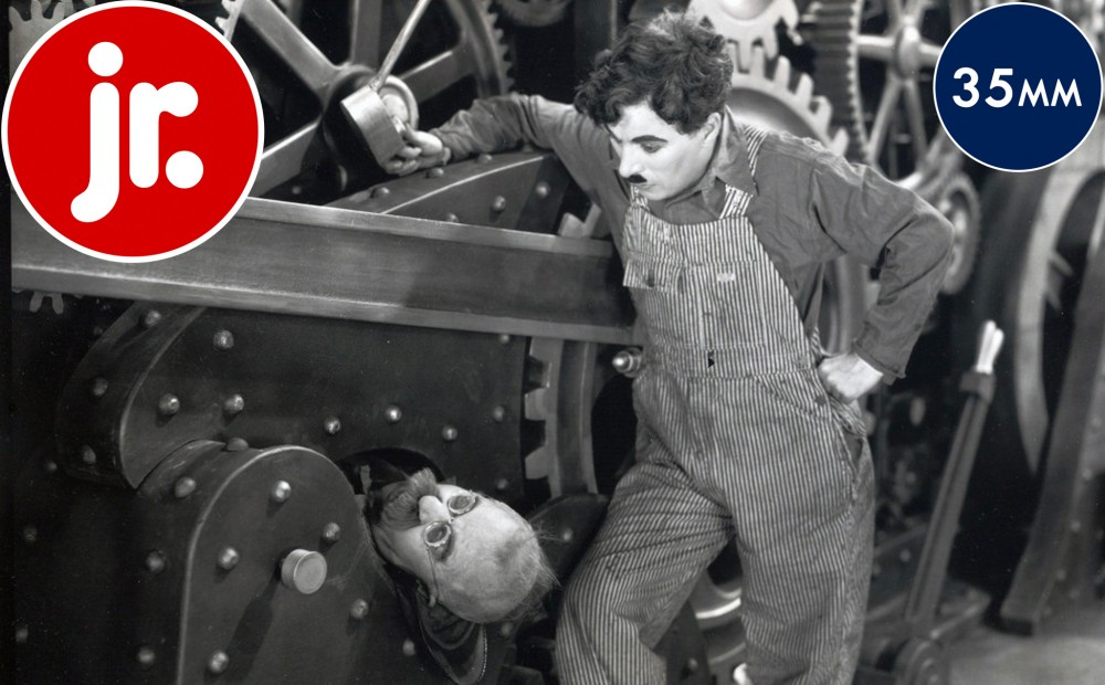 Actor Charlie Chaplin observes another character trapped in a machine, only his head visible.