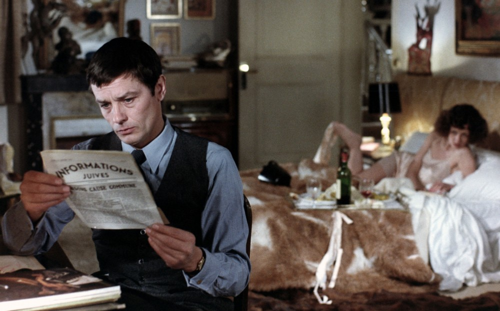 Actor Alain Delon reads a newspaper with the headline