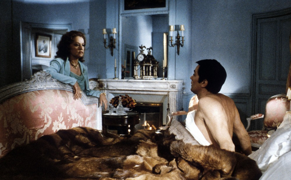 Actor Jeanne Moreau leans over Alain Delon's bed frame; he sits up in bed, shirtless under a fur comforter.
