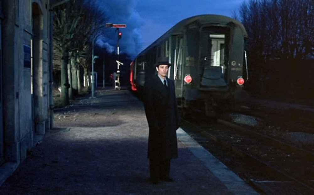 Actor Alain Delon waits on the platform at a train station at twilight.