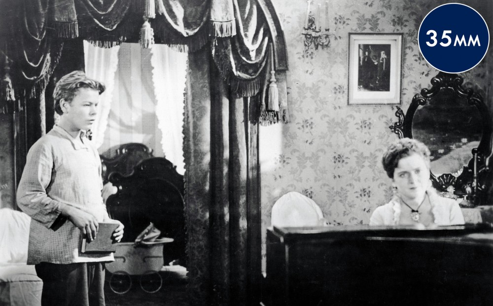 A young boy stands in a parlor with a woman playing piano.