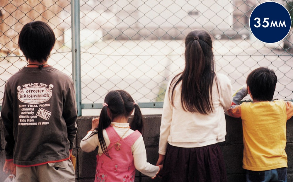 Four children look into a court or playground through a chain-link fence.