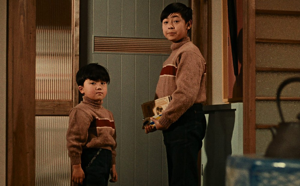 Two young boys in matching sweaters look at something off camera.