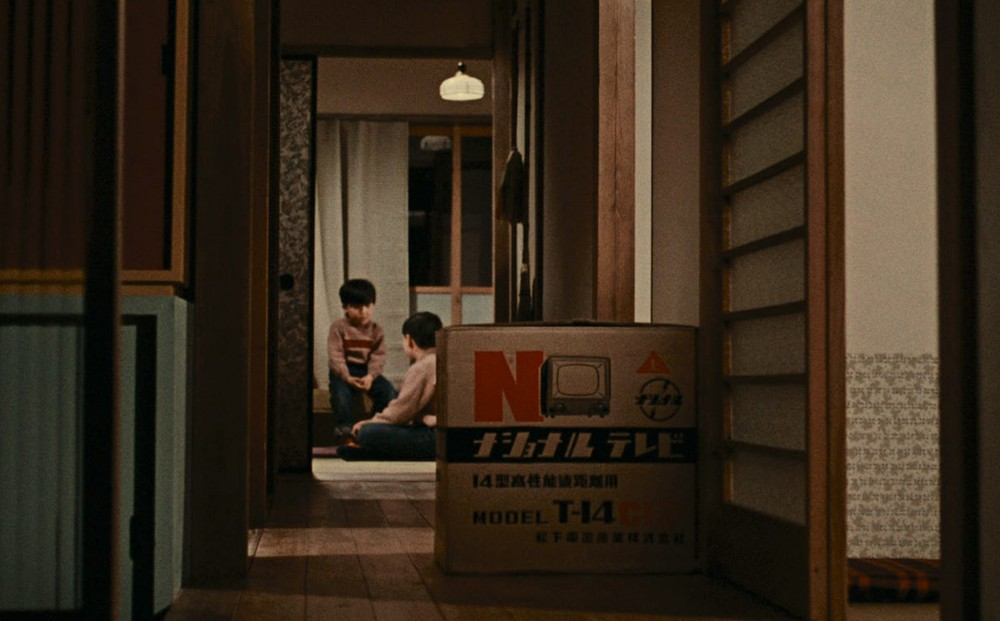 A view of a hallway where a cardboard television box sits; two young boys sit in a room at the end of the hallway.