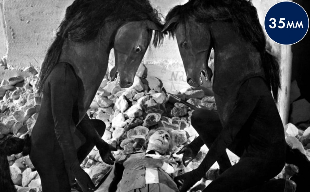 Two human figures in horse costumes kneel beside actor Jean Cocteau, who is laying on rubble.