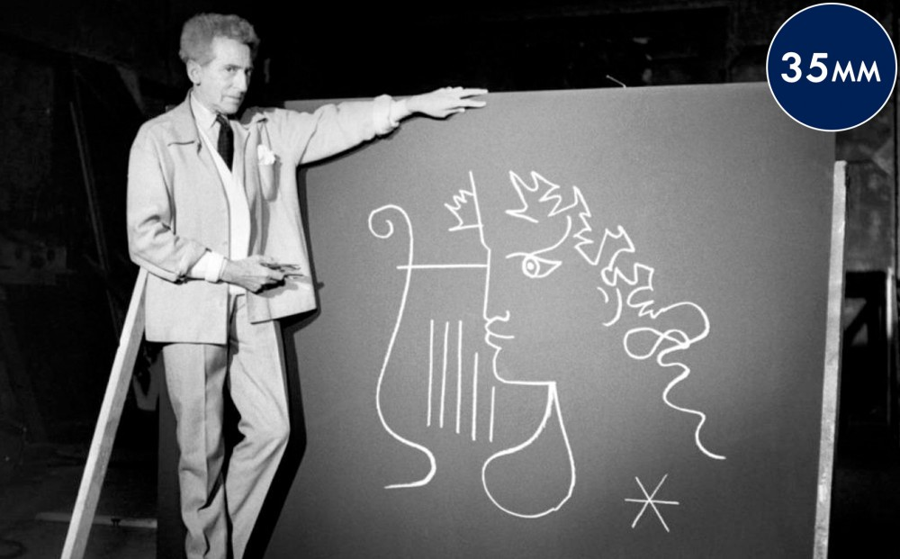 Actor and director Jean Cocteau stands in front of a board with a drawing of a Greek figure.
