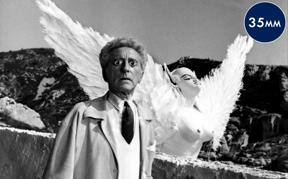 Actor and director Jean Cocteau looks out with a winged bust in the background.