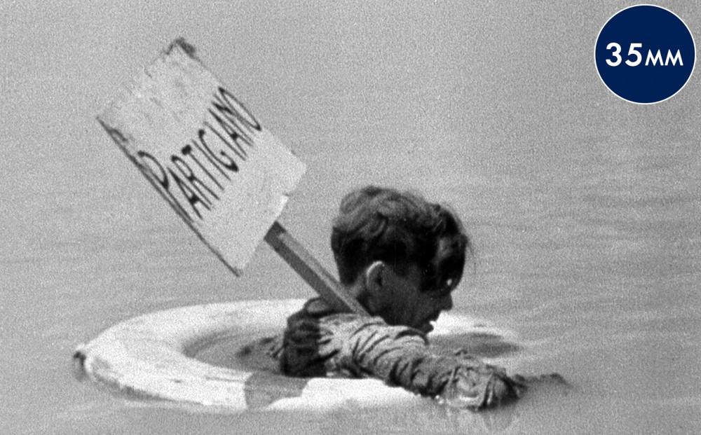 A man in an inner tube, floating in water holds a sign that reads