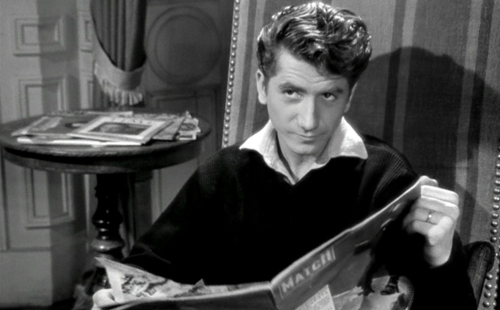 Actor Daniel Gélin looks up from reading a newspaper.