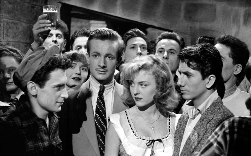 A group of people stand together with main characters conversing in the foreground.