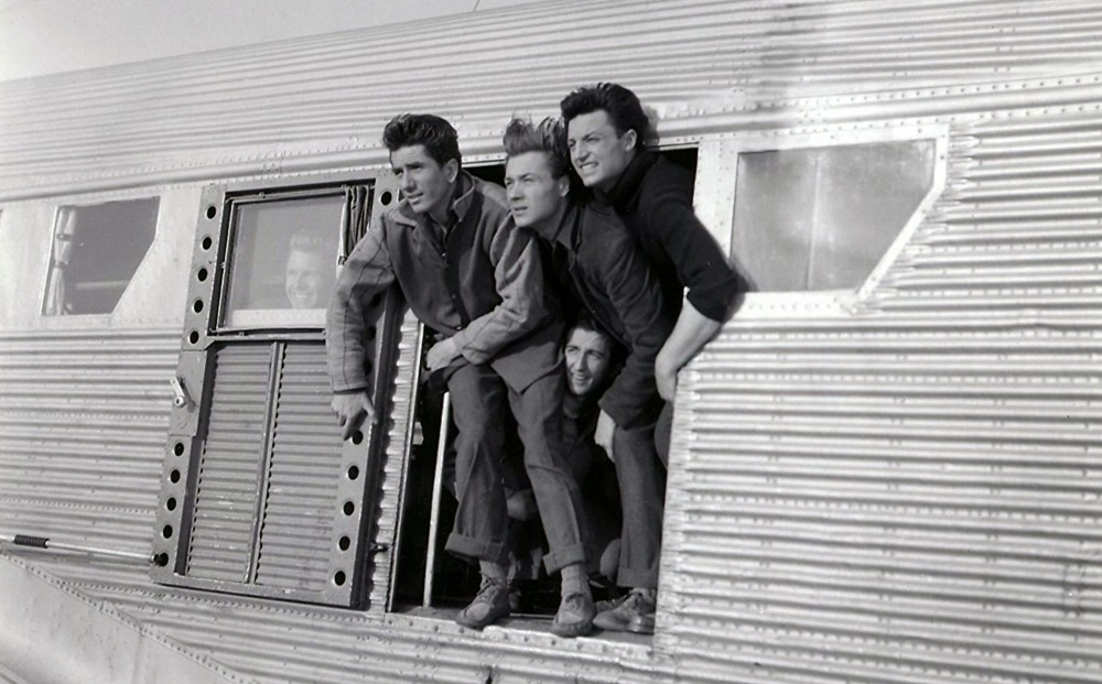 Four men gaze out the open door of a vehicle.