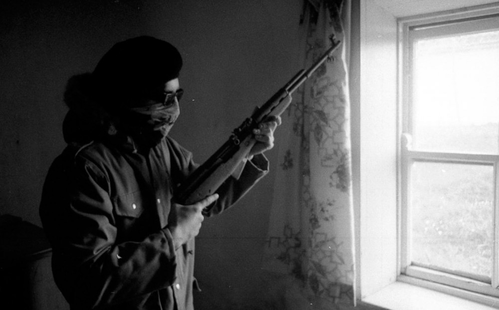 In a room by a window, a person holds a gun; they wear sunglasses and a scarf over their nose and mouth.