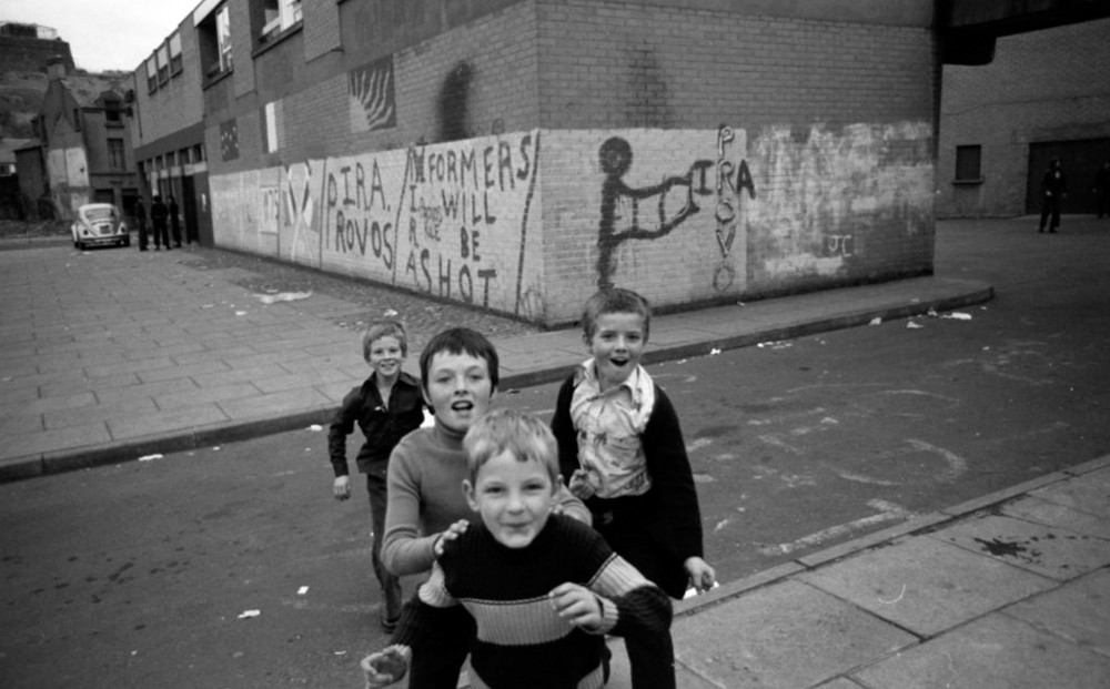 Four children in the street gaze at the camera; a brick wall covered in graffiti is in the background.