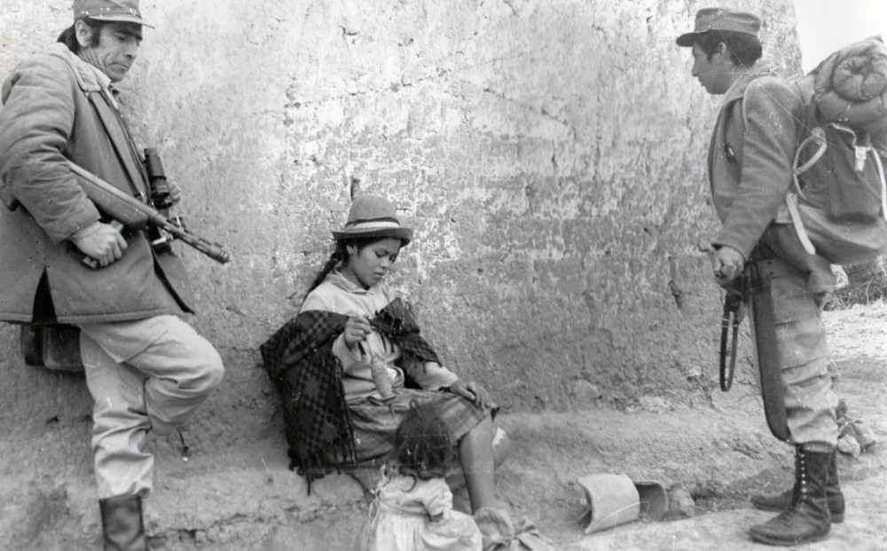 Two men with guns stand by a young woman and child who are sitting by a wall.
