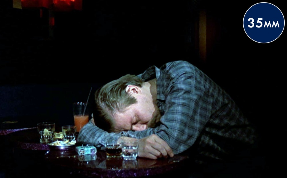A man lays his head on his crossed arms, on a table, next to shot glasses and a pack of cigarettes.