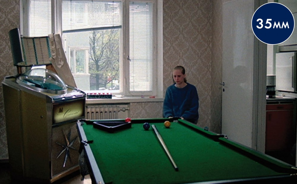 A woman sits forlornly in a room with a large pool table.