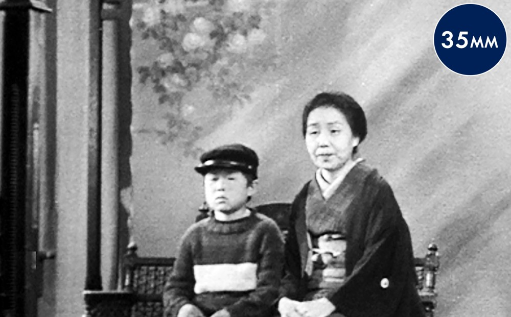 A young boy and a woman sit together, side-by-side on a bench.