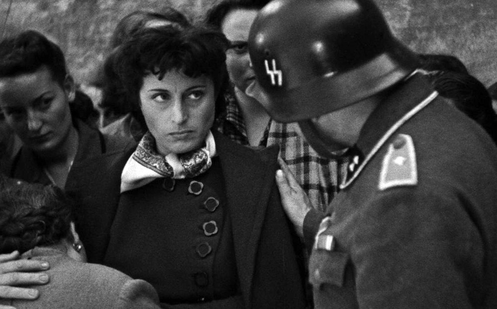 A woman glowers at an SS officer who has his hand on her shoulder.