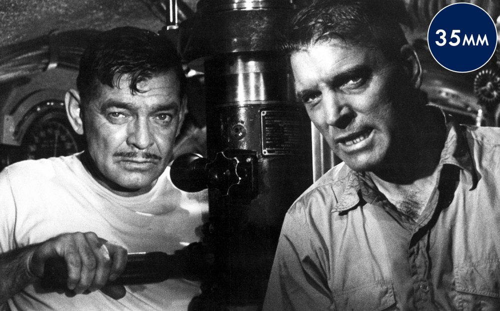 Actors Clark Gable and Burt Lancaster in  a submarine together; Gable holds the handles of a periscope.