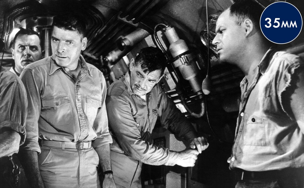 Four men in the submarine look concerned.
