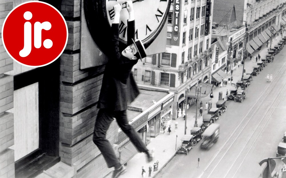 Actor Harold Lloyd hangs onto the hand of a clock, suspended over a city street.
