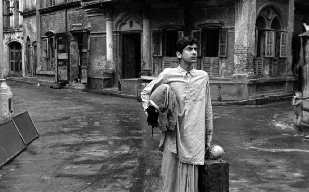 An adolescent Apu, actor Smaran Ghosal, stands in the middle of a street, holding a suitcase.