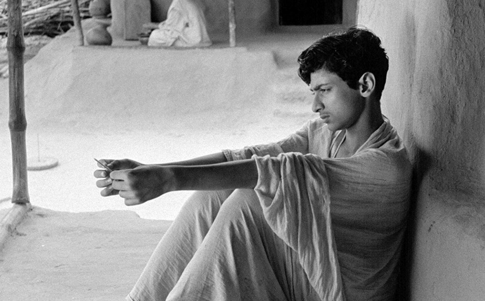 An adolescent Apu, actor Smaran Ghosal, sits while gazing off.