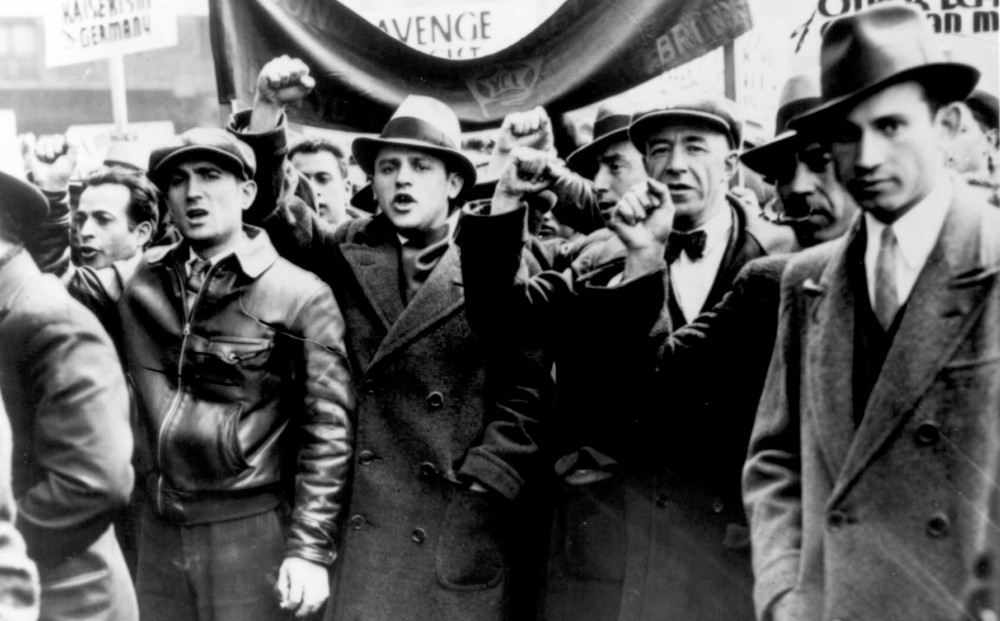 Black and white image of a group of men protesting, some with fists raised.