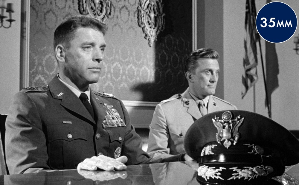Actors Burt Lancaster and Kirk Douglas sit at a table, both wearing military suits.