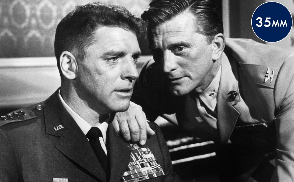 Actor Kirk Douglas has his hand on Burt Lancaster's shoulder, and appears to confide in him.