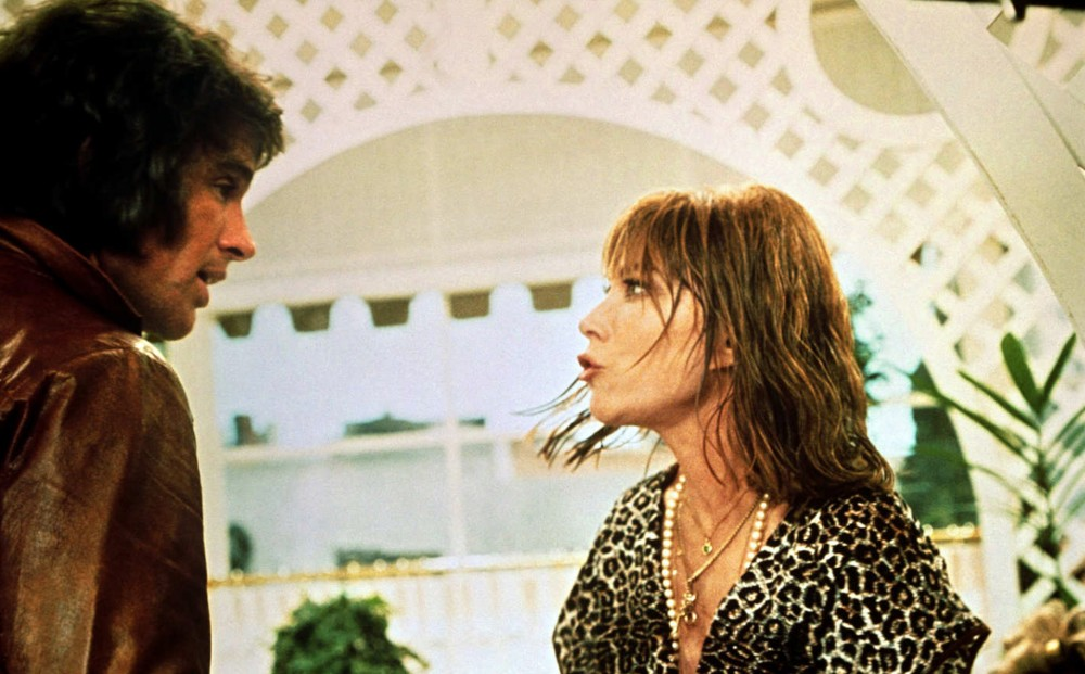 Actor Lee Grant wears a leopard print shirt and multiple necklaces, and has wet hair; she is talking to Warren Beatty, who wears a brown leather jacket.