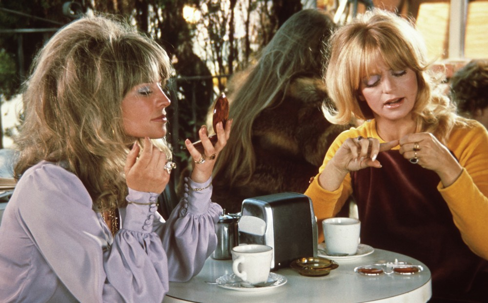 Actors Lee Grant and Goldie Hawn sit at a restaurant table, the latter looking in a hand mirror and the former inspecting her nails